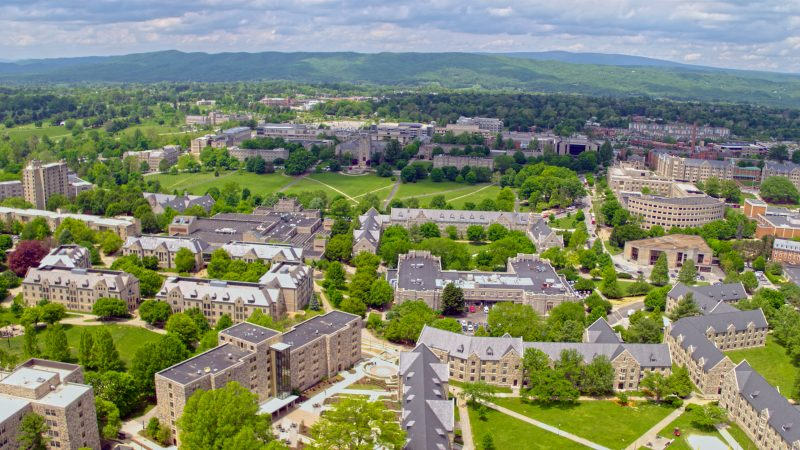 From an aerial view, gray Hokie Stone buildings are tucked between greenery in a mountain valley on a clear, sunny day.